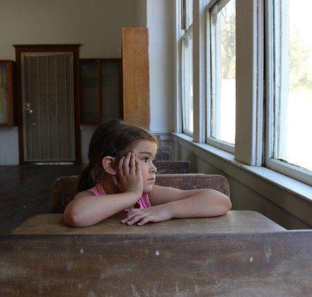 petite fille qui regarde tristement par la fenêtre