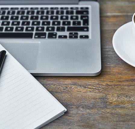 ordinateur avec cahier et stylo