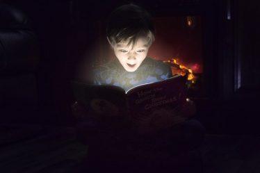 enfant qui lit dans le noir