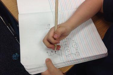 enfant écrit sur un cahier